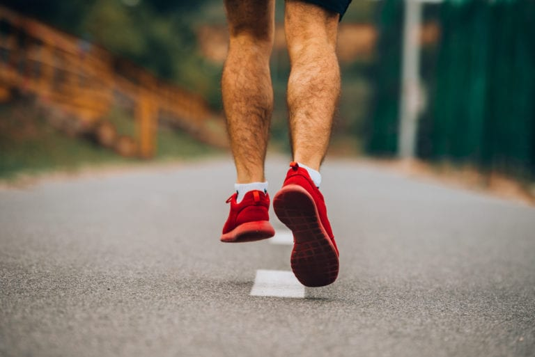 A close-up of a young man with Pes Planus jogging in sneakers